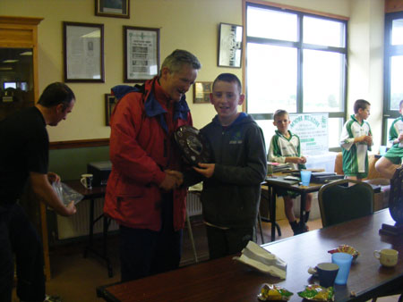 Conor Carney on behalf of local primary schools presenting the Primary Shield to the winning Coolera / Strandhill captain.