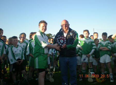 Davy Bannon, chairman of the Fermanagh Hurling Board, presents the under 12 Fermanagh shield to the winning captain Conor Kennedy.
